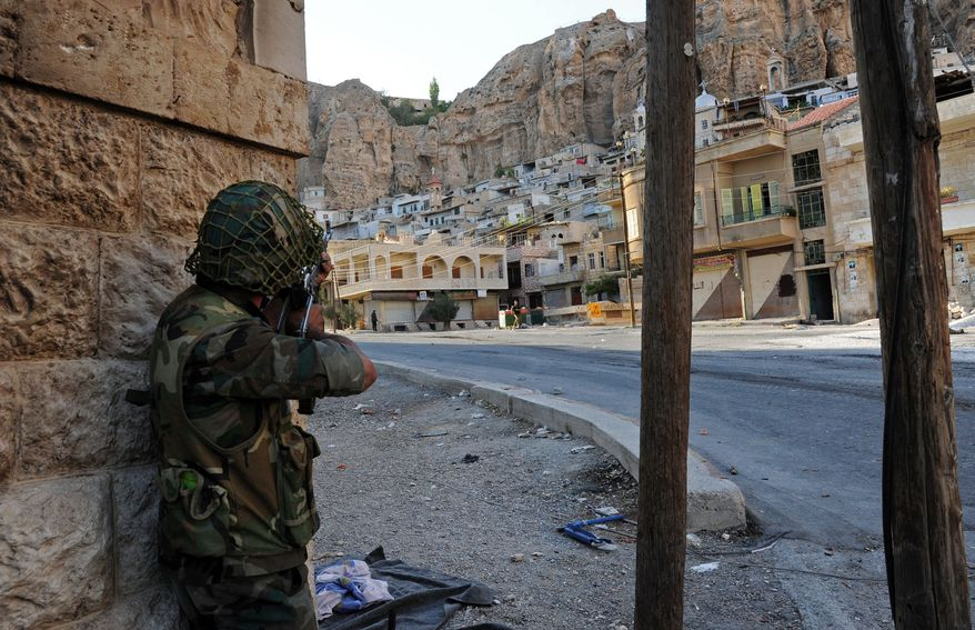 A Syrian government solider aims his weapon during clashes with Free Syrian Army fighters (not pictured) in the ancient, predominantly Christian village of Maaloula, Syria, northeast of the capital, Damascus, on Wednesday, Sept. 11, 2013. Heavy fighting flared as government troops tried to flush out rebel units, including two that are linked to al Qaeda, from the hilltop enclave that they broke into last week. (AP Photo/SANA)