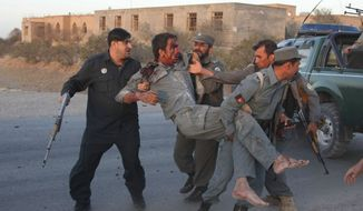 Afghan security personnel assist an injured police after a suicide car bombing and a gunfight near the U.S. Consulate in Herat Province, west of Kabul, Afghanistan, Friday, Sept. 13, 2013. (AP Photo/Hoshang Hashimi)