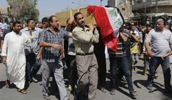 Mourners carry a coffin draped with an Iraqi flag of a man killed Wednesday in a double bomb attack on a Shiite mosque during a funeral procession in Kasra neighborhood in northern Baghdad, Iraq, Thursday, Sept. 12, 2013. A suicide attacker staged a double bombing near a Shiite mosque in northern Baghdad as worshippers were leaving after evening prayers on Wednesday, according to Iraqi authorities. (AP Photo/Khalid Mohammed)