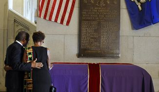 Caleb Pilgrim, left, and Marie Baskerville pray over a casket with the remains of an enslaved man known as Mr. Fortune at the state Capitol in Hartford, Conn., Thursday, Sept. 12, 2013. Mr. Fortune will be honored Thursday with a funeral more than 200 years after he died in Connecticut. (AP Photo/Jessica Hill)