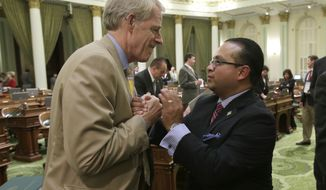 Assemblyman Luis Alejo, D-Watsonville, right, is congratulated by Assemblyman Roger Dickinson after the Assembly approved Alejo's minimum wage bill at the Capitol in Sacramento, Calif., Thursday, Sept. 12, 2013. The bill, AB10, which would raise the minimum wage from the current $8 an hour to $10 by 2016, now goes to the governor. (AP Photo/Rich Pedroncelli)
