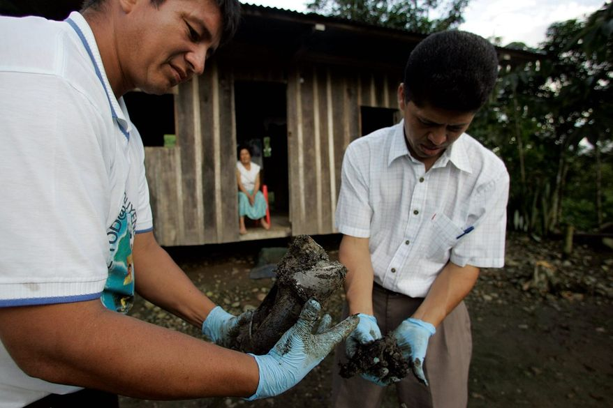 Donald Moncayo (left) and Pablo Fajardo extract mud that contains oil from the yard of Mercedes Jimenez in Lago Agrio, Ecuador, in 2008. Ecuadorean President Rafael Correa has sided squarely with the 30,000 plaintiffs, Indians and colonists in a class-action lawsuit, dubbed an Amazon Chernobyl by environmentalists, over the slow poisoning of a Rhode Island-sized expanse of rain forest. (Associated Press)