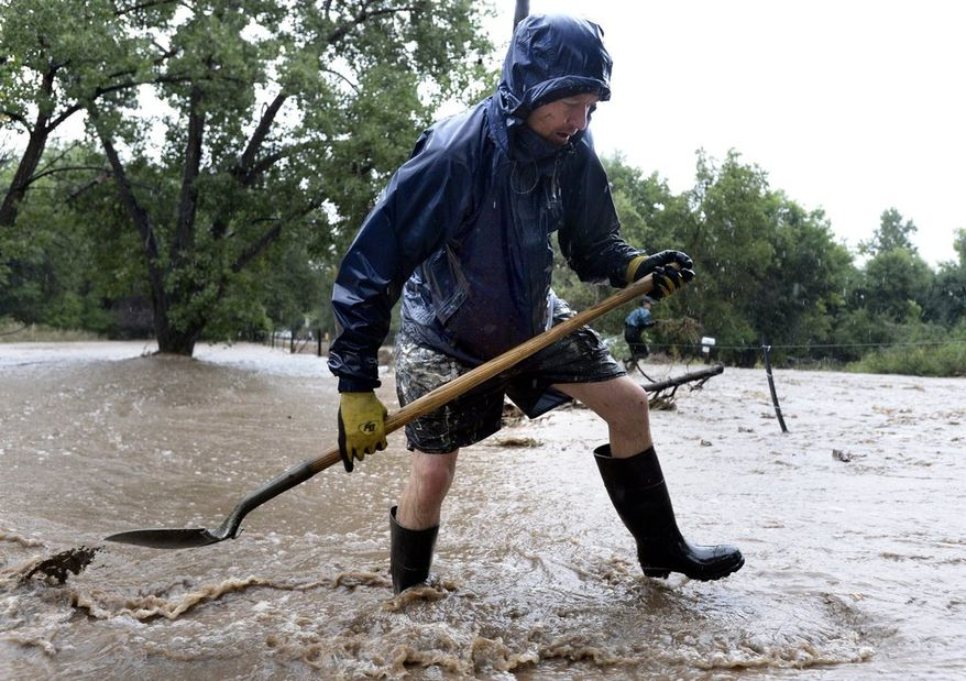 DISASTER DEEPENS: Dean Beacom works to save his home in Boulder, Colo., on Sunday. The National Weather Service said     1 to 3 inches of rain created a risk of more flooding and mudslides. The disaster has hit 15 counties along the Rocky Mountains. (Associated Press)