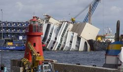 A lighthouse is seen in front of the Costa Concordia cruise ship as it lies on its side off the Tuscan island of Giglio on Sunday, Sept. 15, 2013. On Monday, an international team of engineers is expected to try a never-before-attempted procedure to set upright the luxury liner, which capsized after striking a reef in 2012, killing 32 people. (AP Photo/Andrew Medichini)