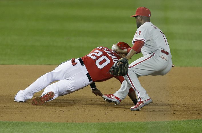 Philadelphia Phillies shortstop Jimmy Rollins (11) tags Washington Nationals Ian Desmond (20) for an out in the third inning of a baseball game at Nationals Park, Saturday, Sept. 14, 2013, in Washington. (AP Photo/Pablo Martinez Monsivais)