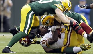 Washington Redskins quarterback Robert Griffin III loses his helmet as he is sacked by Green Bay Packers' Clay Matthews and A.J. Hawk during the first half of an NFL football game Sunday, Sept. 15, 2013, in Green Bay, Wis. (AP Photo/Tom Lynn)