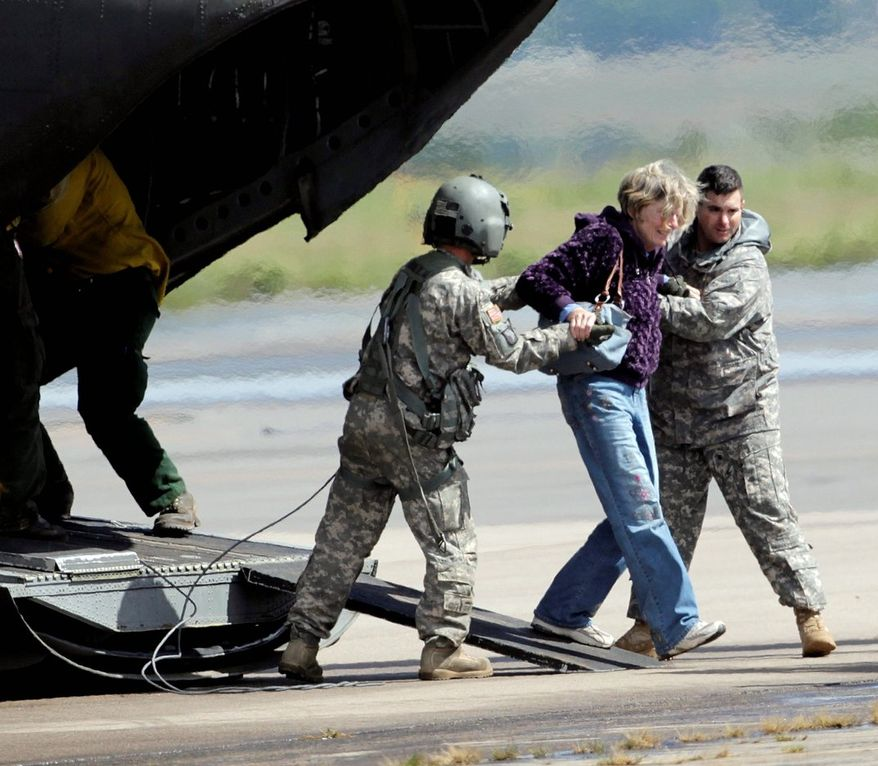 A woman is helped off of a military helicopter at the Boulder Municipal Airport in Boulder, Colo., on Monday after being rescued. Thousands of people remained stranded by high water and washed out roads in the state after flooding.
