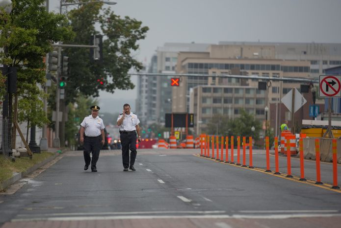 Two police officers walk down M st. outside of the Navy Yard. Recreation centers and parks in the area also clos