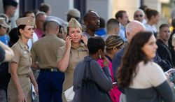 Family and friends wait to greet staff of the Naval Sea Systems Command headquarters as they are bused from the Washington Navy Yard to Nationals Park, in Washington, Monday, Sept. 16, 2013. At least one gunman launched an attack inside the Washington Navy Yard, spraying gunfire on office workers in the cafeteria and in the hallways at the heavily secured military installation in the heart of the nation's capital, authorities said. (AP Photo/Jacquelyn Martin)