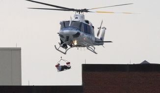 A U.S. Park Police helicopter removes a man in a basket from the Washington Navy Yard on Sept. 16, 2013. Earlier in the day, the U.S. Navy said it was searching for an active shooter at the Naval Sea Systems Command headquarters, where about 3,000 people work. The exact number of people killed and the conditions of those wounded was not immediately known. (Associated Press)