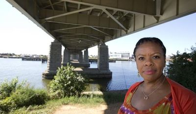 "Alesia Tisdall stands for a photograph under the Frederick Douglass Memorial Bridge which spans the Anacostia River in Washington on Friday, Sept. 6, 2013. Tisdall, who drove daily over the bridge for 15 years but now crosses it only occasionally, said she found it unnerving that the bridge would ""bounce"" in the middle as she sat in bumper-to-bumper traffic. (AP Photo/Alex Brandon)"