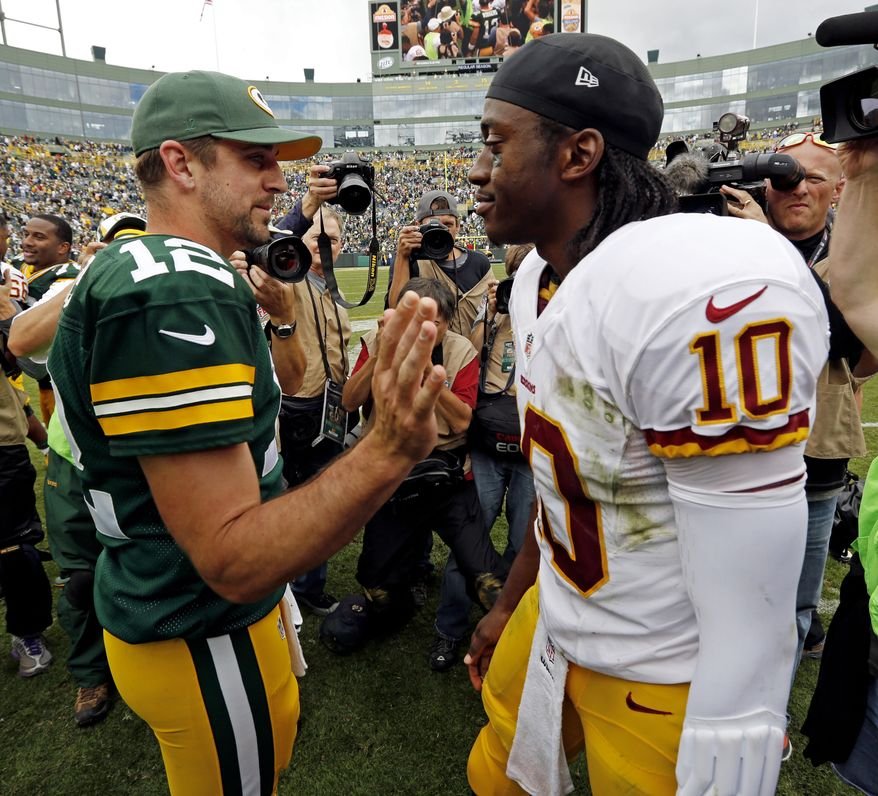 Green Bay Packers quarterback Aaron Rodgers (12) talks to Washington Redskins quarterback Robert Griffin III after an NFL football game Sunday, Sept. 15, 2013, in Green Bay, Wis. The Packers won 38-20. (AP Photo/Mike Roemer)