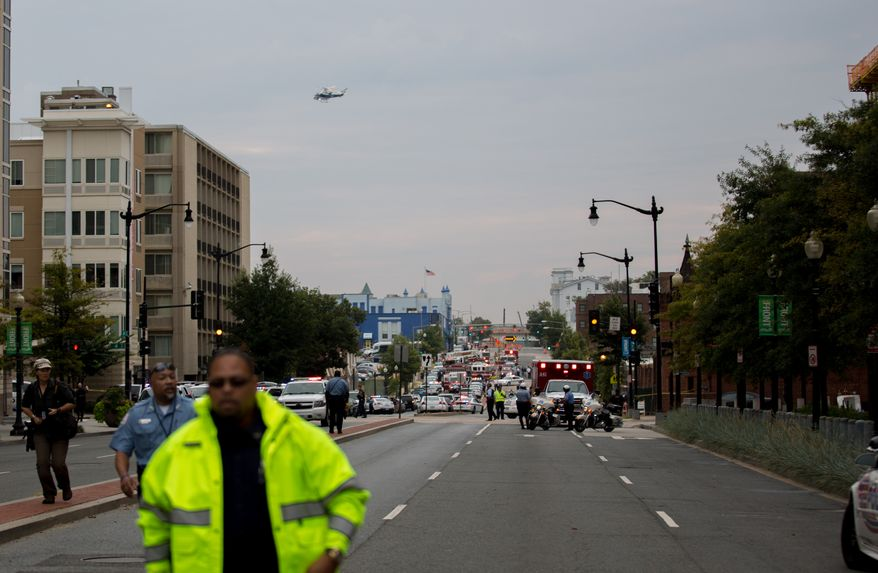 A helicopter circles overhead at the Navy Yard as workers are evacuated from the area where police are searching for a gunman, in Washington, D.C.,  Monday, Sept. 16, 2013.  (Andrew S. Geraci/The Washington Times)