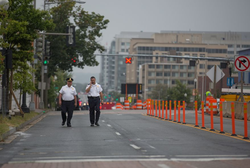 Two police officers walk down M Street Southwest outside the Washington Navy Yard on Monday, Sept. 16, 2013.  (Andrew S. Geraci/The Washington Times)