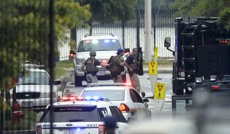 Law enforcement personnel are seen through the gate into the Washington Navy Yard in Washington on Sept. 16, 2013. At least one gunman opened fire inside a building at the Navy Yard, and officials said several people were killed and more were wounded, including a law enforcement officer. (Associated Press)