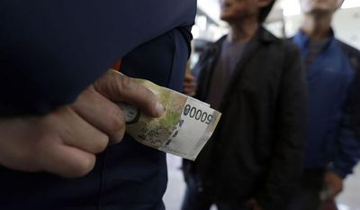 South Koreans hold South Korean won while waiting to exchange money in front of a bank before leaving for the Kaesong Industrial Complex at the Inter-Korean Transit Office near the border village of Panmunjom, which has separated the two Koreas since the Korean War, in Paju, north of Seoul, South Korea, Monday, Sept. 16, 2013. (AP Photo/Lee Jin-man)