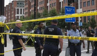 Police work the scene on M Street SE in Washington near the Washington Navy Yard on Monday, Sept. 16, 2013. Police and emergency crews gathered Monday morning outside the Naval Sea Systems Command Headquarters building, where the shooting was reported. (AP Photo/Jacquelyn Martin)