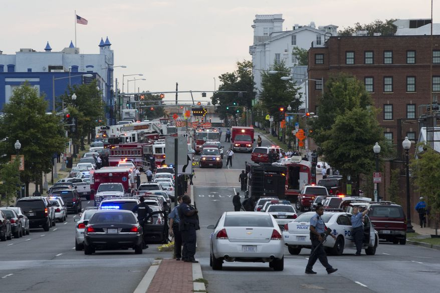 Police work the scene on M Street Southeast in Washington after a gunman was reported at the Washington Navy Yard on Monday, Sept. 16, 2013. (AP Photo/Jacquelyn Martin)