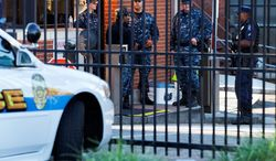 An officer who said he was with the Department of Defense (right) and Navy personnel stand guard inside the gate of the closed Washington Navy Yard on Tuesday. (ASSOCIATED PRESS)