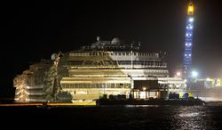 """The Costa Concordia is seen after it was lifted upright off Italy's Giglio Island early on Tuesday, Sept. 17, 2013. The shipwrecked cruise vessel was pulled completely upright after a complicated, 19-hour operation to wrench it from its side, where it capsized last year off Tuscany, with officials declaring the maneuver a """"perfect"""" end to a daring and unprecedented engineering feat. (AP Photo/Andrew Medichini)"""