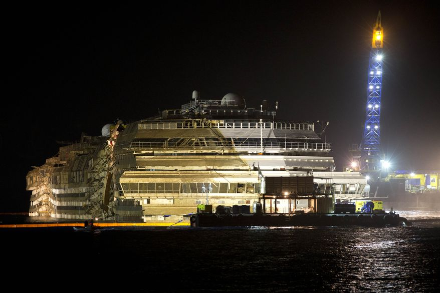 "The Costa Concordia is seen after it was lifted upright off Italy's Giglio Island early on Tuesday, Sept. 17, 2013. The shipwrecked cruise vessel was pulled completely upright after a complicated, 19-hour operation to wrench it from its side, where it capsized last year off Tuscany, with officials declaring the maneuver a ""perfect"" end to a daring and unprecedented engineering feat. (AP Photo/Andrew Medichini)"