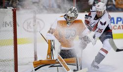 Philadelphia Flyers goalie Ray Emery, left, blocks a shot as Washington Capitals' Jason Chimera slides in during the first period of a preseason NHL hockey game, Monday, Sept. 16, 2013, in Philadelphia. (AP Photo/Matt Slocum)
