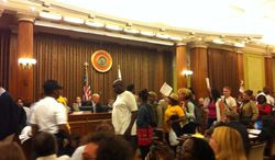 """Protesters exit the D.C. Council chambers after members failed to override the mayor's veto of the """"living wage"""" bill. (Andrea Noble/The Washington Times)"""