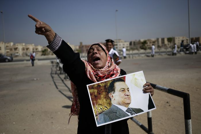 An Egyptian woman carrying a photo of ousted president Hosni Mubarak chants slogans against ousted President Mohammed Morsi and the Muslim Brotherhood as she expresses her support for Mubarak at a court in Cairo, Egypt, Saturday, Sept. 14, 2013. (AP Photo/Hassan Ammar)