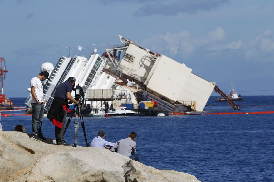 A television crew films the Costa Concordia ship as it lies on its side on the Tuscan Island of Giglio, Italy, early Monday morning, Sept. 16, 2013. An international team of engineers is trying a never-before attempted strategy to set upright the luxury liner, which capsized after striking a reef in 2012 killing 32 people. (AP Photo/Andrew Medichini)