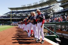 Holding Navy hats, Washington Nationals manager Davey Johnson, right, and others observe a moment of silence before a baseball game against the Atlanta Braves at Nationals Park Tuesday, Sept. 17, 2013, in Washington. The Nationals wore Navy hats, presented to them by Adm. James A. Winnefield, vice-chairman of the Joint Chiefs of Staff, before the game, to honor those killed and injured in the attack Monday at the nearby Washington Navy Yard. (AP Photo/Alex Brandon)