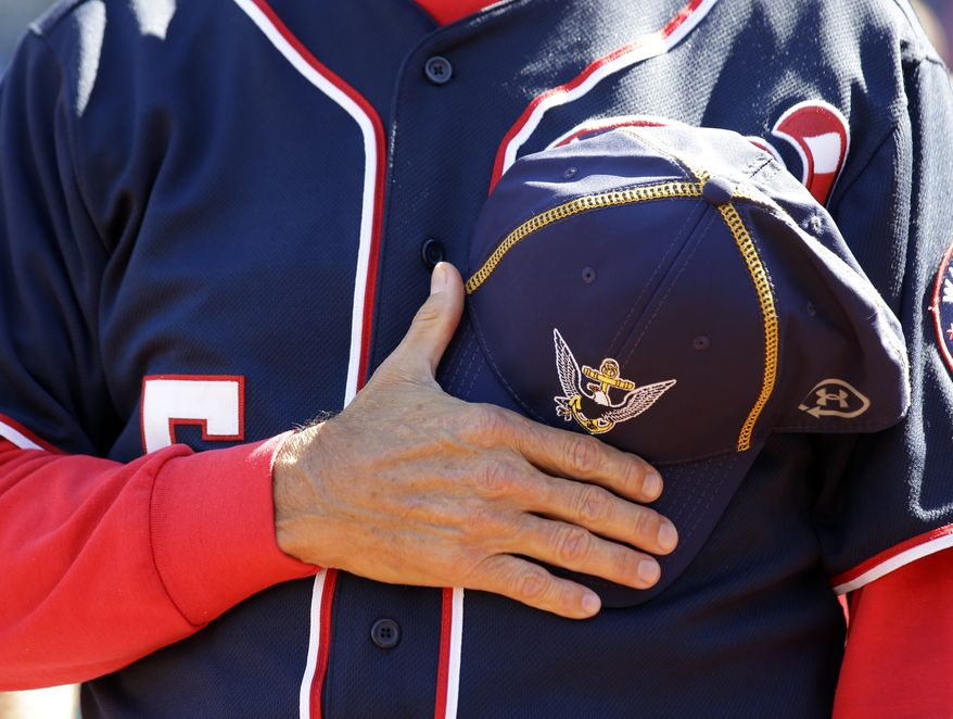 Washington Nationals manager Davey Johnson holds a Navy hat over his heart during a moment of silence before a baseball game against the Atlanta Braves at Nationals Park Tuesday, Sept. 17, 2013, in Washington. The Nationals wore Navy hats, presented to them before the game, by Adm. James A. Winnefield, vice-chairman of the Joint Chiefs of Staff,  to honor those killed and injured in the attack Monday at the nearby Washington Navy Yard. (AP Photo/Alex Brandon)