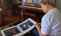 Patricia Arnold of Rochester, Mich., looks at pictures that include her son Michael Arnold, 59, who was among the 12 people killed Monday at the Navy Yard. (Detroit News Via Associated Press)