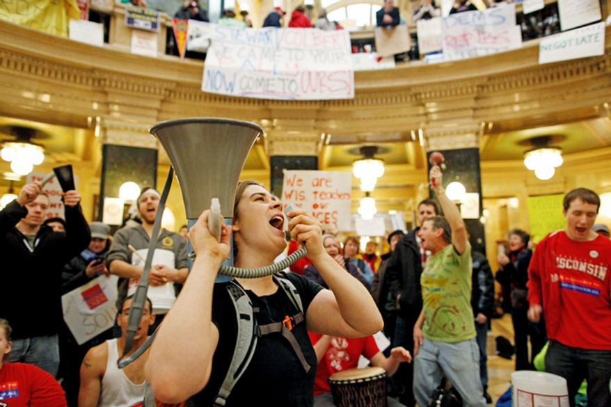 ** FILE ** Protesters bang drums and shout slogans inside the state Capitol Monday, Feb. 21, 2011, in Madison, Wis. Opponents to Gov. Scott Walker's bill to eliminate collective bargaining rights for many state workers are taking part in their seventh day of protesting. (AP Photo/Jeffrey Phelps)