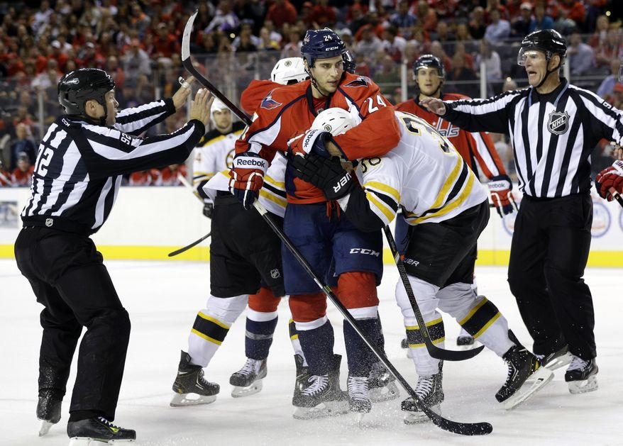 Officials break up a scuffle between Washington Capitals left wing Aaron Volpatti (24) and Boston Bruins left wing Jordan Caron in the third period of a preseason NHL hockey game, Tuesday, Sept. 17, 2013, in Baltimore. (AP Photo/Patrick Semansky)