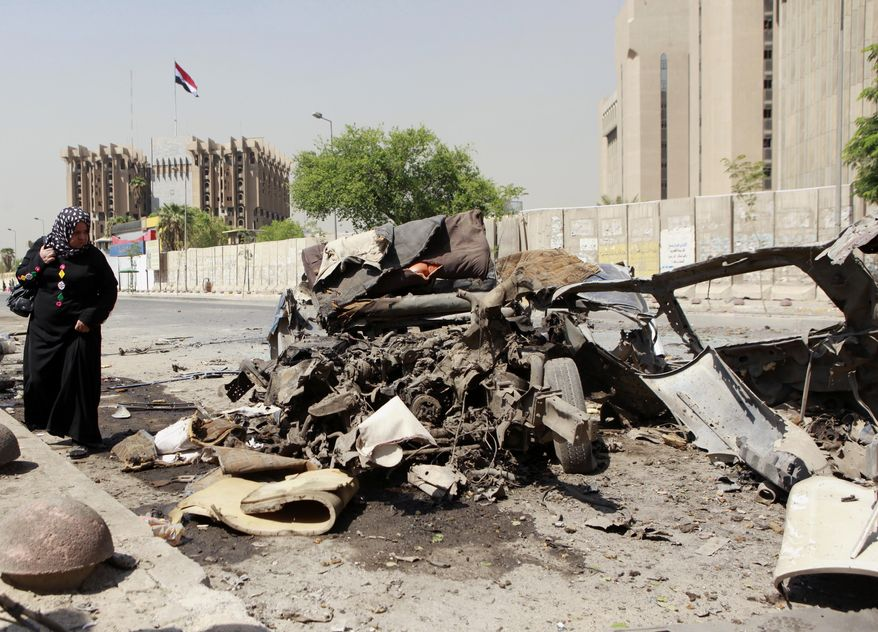 A woman inspects the site of a car bomb attack in front of the Ministry of Higher Education and Scientific Research in central Baghdad on Sept. 18, 2013. More than 4,000 people have been killed since April, including more than 800 just in August, according to U.N. figures. (Associated Press)