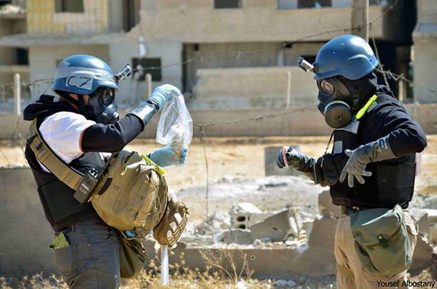 In this Aug. 28, 2013, citizen journalism image provided by the United Media Office of Arbeen, which has been authenticated based on its contents and other AP reporting, members of the U.N. investigation team take samples from sand near a part of a missile that is likely to be one of the chemical rockets according to activists, in the Damascus countryside of Ain Terma, Syria. (AP Photo/United Media Office of Arbeen)