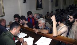 ** FILE ** In this Sept. 1, 2012, file photo, Syrian prisoners sign their papers of release at the Damascus Police Command headquarters in Damascus, Syria. (AP Photo/Bassem Tellawi, File)