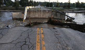 On Tuesday, Sept. 17, 2013, St. Vrain Creek in Longmont, Colo., flows past a bridge destroyed in flooding days earlier. (AP Photo/Brennan Linsley)