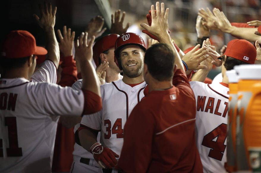 Washington Nationals outfielder Bryce Harper is greeted by his teammates after hitting his 20th home run of the season, a three-run shot in the Nationals' 3-2 win over the Marlins. (Associated Press photo)