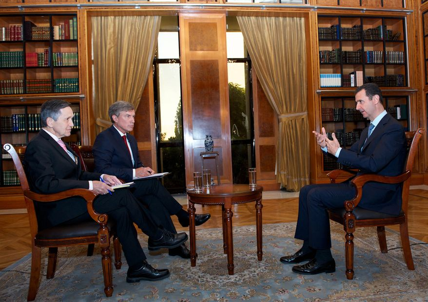 Syrian President Bashar Assad (right) talks with Dennis J. Kucinich (left) and Greg Palkot of the Fox News Channel in Damascus, Syria, on Tuesday, Sept. 17, 2013. (AP Photo/SANA)