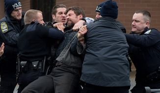 """Hugh Jackson, playing the father of a missing girl, has to be restrained by police in """"Prisoners."""" Jake Gyllenhaal (third from left) is the police detective trying to solve the case. (WARNER BROTHERS PICTURES VIA ASSOCIATED PRESS)"""