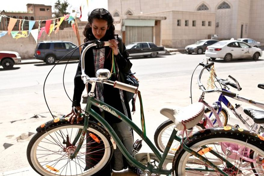 "The title character in ""Wadjda"" hides colorful hair barrettes under a black abaya, secretly paints her toenails and yearns to own and ride a colorful bicycle. (tribeca film festival via associated press)"