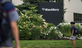 **FILE** Pedestrians walk near BlackBerry's headquarters in Waterloo, Ontario, on the morning of the company's Annual General Meeting on July 9, 2013. (Associated Press/The Canadian Press)