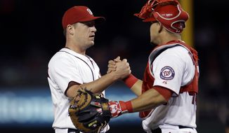 Washington Nationals catcher Wilson Ramos, right, and starting pitcher Jordan Zimmermann celebrate their win against the Miami Marlins during a baseball game at Nationals Park in Washington, on Friday, Sept. 20, 2013. Zimmermann pitched a two-hit complete game shut out earning the Nationals a win of 8-0. (AP Photo/Jacquelyn Martin)