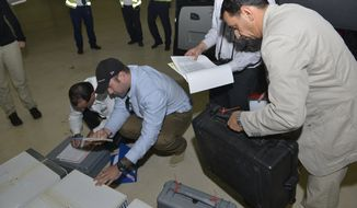 """** FILE ** In this file photo released Saturday Aug. 31, 2013, by the Organization for the Prohibition of Chemical Weapons, samples brought back by the U.N. chemical weapons inspection team are checked in upon their arrival at The Hague, Netherlands. Syria has sent the Organization for the Prohibition of Chemical Weapons an """"initial declaration"""" outlining its weapons program, the organization said Friday Sept. 20, 2013. (AP Photo/OPCW, Henry Arvidsson, File)"""