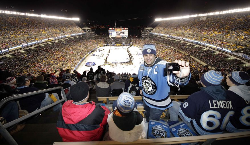 Pittsburgh Penguins fan Ben Alper of Wexford, Pa., takes his picture from the top row of Heinz Field during warm ups before the NHL Winter Classic outdoor hockey game between the Pittsburgh Penguins and Washington Capitals in Pittsburgh, Saturday, Jan. 1, 2011. (AP Photo/Gene J. Puskar)