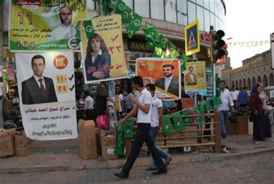 People walk past election campaign posters of different parties, in Irbil, Iraq, 350 kilometers (217 miles) north of Baghdad, Friday, Sept. 20, 2013, day ahead of the self-ruled northern Kurdish region's fourth election for local parliament since 1992. (AP Photo/ Khalid Mohammed)