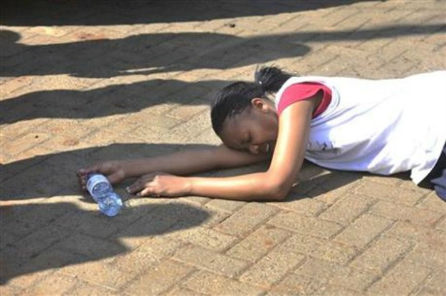 ** FILE ** A rescued hostage collapses on the ground after being freed by police at Westgate Mall in Nairobi, Kenya Saturday, Sept. 21, 2013, after gunmen threw grenades and opened fire during an attack that left multiple dead and dozens wounded. (AP Photo/Riccardo Gangale)