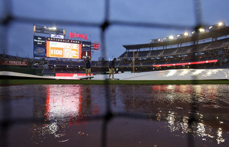 The Washington Nationals' grounds crew squeegees water off the tarp during a three-hour, 49-minute rain delay on Saturday night. The game was postponed until Sunday night. (Associated Press photo)