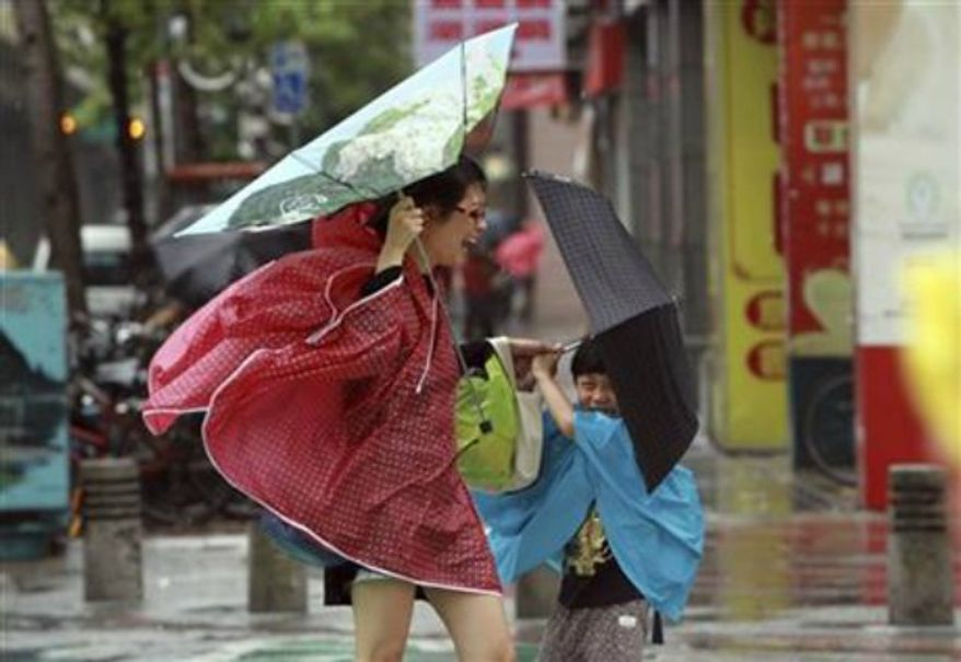 A woman and her child hold their umbrellas tight against powerful gusts of wind as typhoon Usagi approaches in Taipei, Taiwan, Saturday, Sept. 21, 2013. (Associated Press)